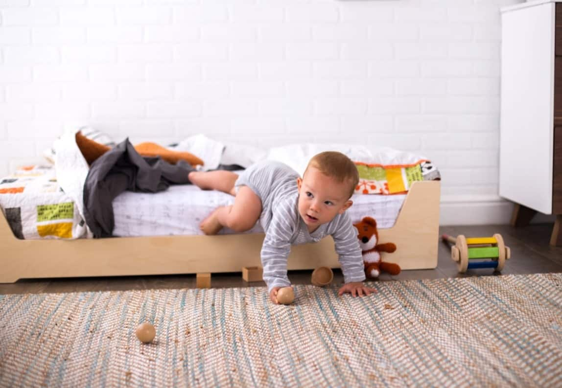 toddler crawling out of a floor bed